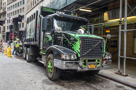 municipal editorial: New York, August 17, 2016: Men are working on collecting garbage in their truck in downtown Manhattan.