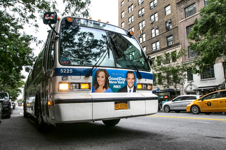 An MTA bus stands idle with lights flashing in the street in Manhattan. Editorial