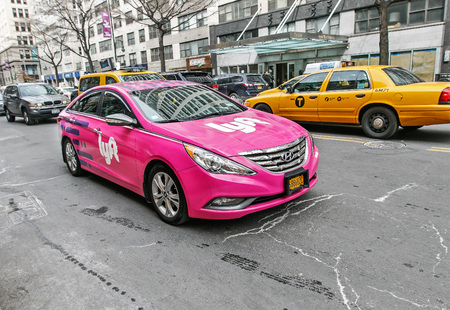 New York, March 11, 2017: A pink car with Lyft logo is driving along 14th street in Manhattan. Lyft offers a convenient way to hire a ride using a smartphone.