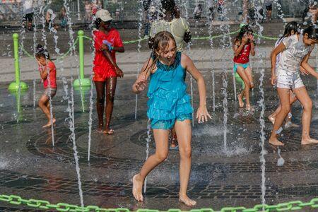 New York, 10 augustus 2017: Kinderen worden drijfnat tijdens het spelen met een fontein tijdens een hete zomerdag.
