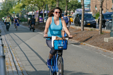 New York, August 10, 2017: Young woman is riding a Citibike on the bicycle lane that runs along the western edge of Manhattan.