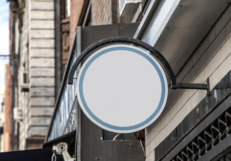 Generic white round sign attached to an exterior wall.