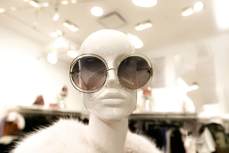 Closeup of a female mannequin wearing an oversized round sunglasses and a fur coat.