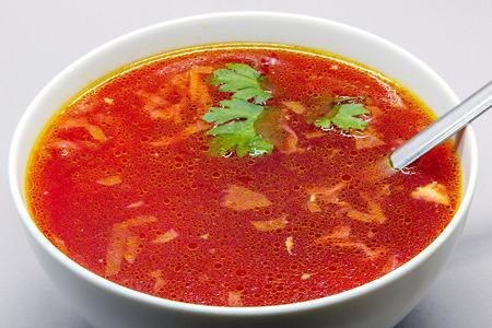 Borscht, Russian beet soup, in a white bowl.