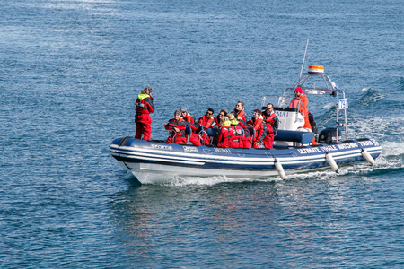 Reykjavik, Iceland, August 20, 2017: Tourists are coming back to harbor from a whale watching tour on a small speed boat. All are wearing matching warm overalls provided by the outfitter. Редакционное