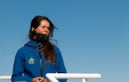 Reykjavik, Iceland, August 20, 2017: A female whale watching tour guide is speaking into her microphone during one of the tours. Editorial