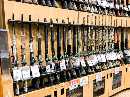 Hunting rifles stand on a shelf in a Dick's Sporting Goods store. Editorial