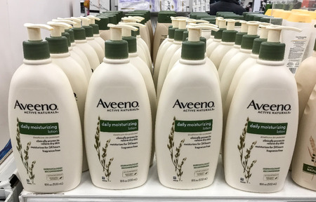 New York, October 23, 2017: Bottles of Aveeno moisturizing lotion stand on a store shelf.