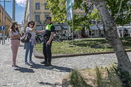 Lisbon, Portugal, May 6, 2018: A couple of tourists are asking a policeman for dicrections.