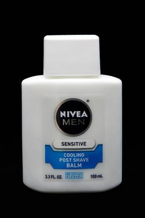 Bottle of Nivea Sensitive post shave balm for men against black background.