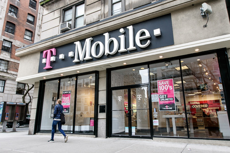 New York, January 21, 2017: Woman is walking by a T Mobile store in Manhattan.