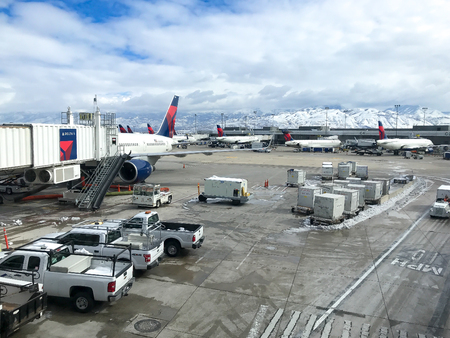 Salt Lake City, March 5, 2018: View of the SLC airport tarmac with vehicles and Delta airplaines.