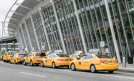 New York, May 5, 2018: Yellow taxi cabs have formed a line in front of JFK airports terminal 4.