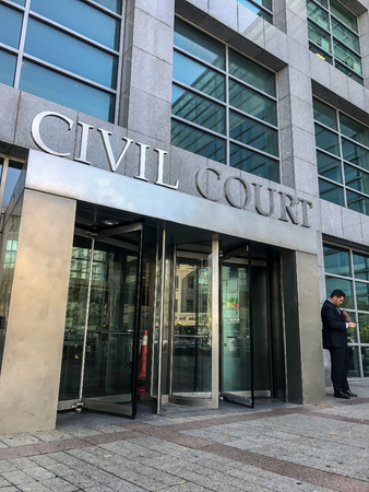 New York, September 25, 2017: A man is standing near the front entrance to the Civil Court of Queens County. 에디토리얼