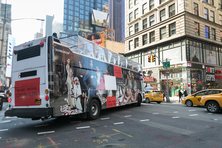 New York, March 15, 2018: Tourist double decker bus with a Calvin Klein advert is making a turn into 7th Avenue in Manhattan. 에디토리얼