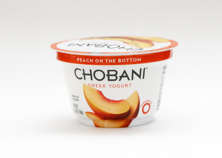 New York, January 23, 2017: A container of peach Chobani greek yogurt stands against white background.