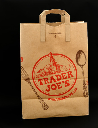 New York, June 13, 2017: Brown paper bag from Trader Joes grocery store stands against black background. 에디토리얼