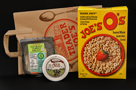 New York, June 13, 2017: Small sampling of food items purchased from Trader Joes grocery store along with a branded brown paper bag stand against black background.