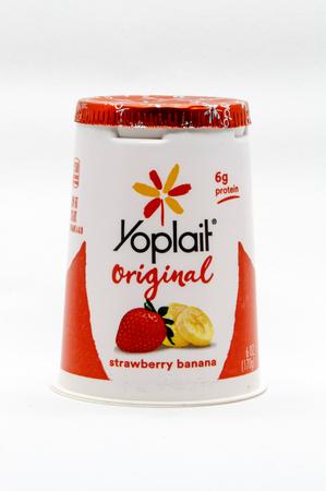 New York, November 10, 2017: Yoplait strawberry banana yogurt stands against white background.