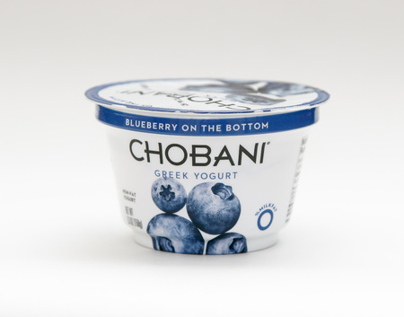 New York, January 23, 2017: A container of blueberry Chobani greek yogurt stands against white background.