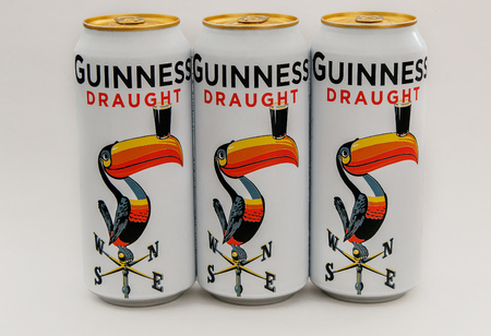 New York, August 8, 2017: Three limited edition Guiness beer cans stand against white background.