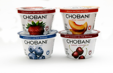 New York, January 23, 2017: Four containers of Chobani greek yogurt of different flavors stand against white background. 에디토리얼