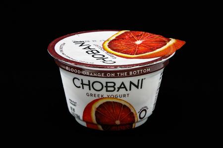 New York, December 4, 2017:  Tub of Chobani blood orange yogurt stands against black background.