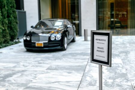 New York, 10202017: Notice stands near the entrance to the posh 432 Park Avenue residential tower in NYC with a black Bentley parked next to the entrance.