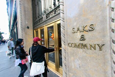 People are walking into the flagship Saks Fifth Avenue department store on Fifth Avenue in New York City. Editorial