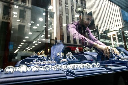 A jewelry store employee is setting up the stores front window before the store opens for the day. Diamond district of NYC. Editorial