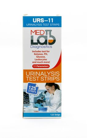 Pack of urinalysis test strips against white background.