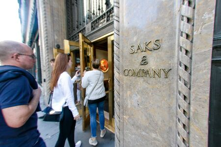 People are walking into the flagship Saks Fifth Avenue department store on Fifth Avenue in New York City. Imagens - 133574737