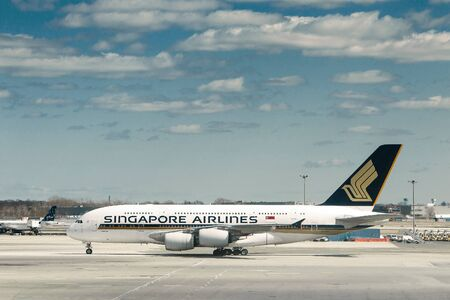 New York, 3/17/2019: Singapore Airlines commercial jet is maneuvering on the tarmac at JFK airport. Imagens - 133574747
