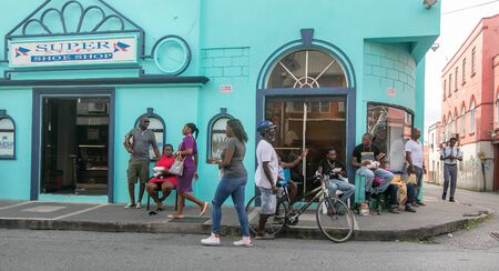 Locals hang out by a shoe store in Bridgetown, Barbados.