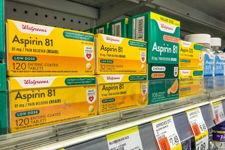 New York, 2/27/2019: Packs of Aspirin stand on a shelf at a Walgreens pharmacy. Фото со стока - 133574752