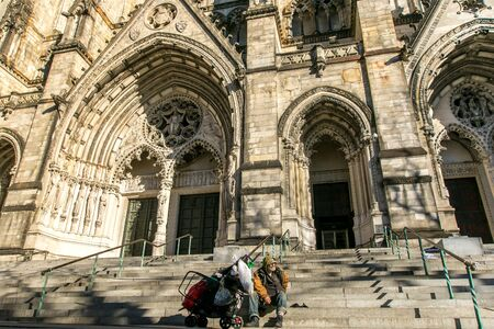 Unidentified homeless man has situated himselft and his belongings at the steps leading to the portals of The Cathedral Church of St. John the Divine in Manhattan. Imagens - 133574757