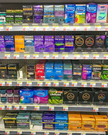 New York, 2/27/2019: Packs of various condoms stand on a shelf of a Walgreens drug store. Imagens - 133574774