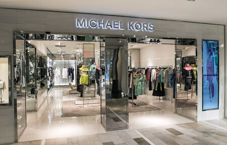New York, 3/11/2019: Dresses and other clothing items hang at the Michael Kors section at Bloomingdale's department store in Manhattan awaiting attention from customers. Imagens - 133574792