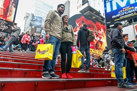 Tourist couple is posing for a picture at the heart of Times Square. Editorial
