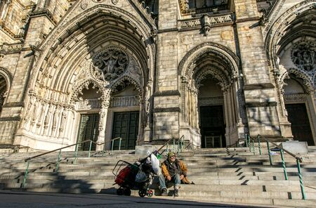 Unidentified homeless man has situated himselft and his belongings at the steps leading to the portals of The Cathedral Church of St. John the Divine in Manhattan. Imagens - 133574797