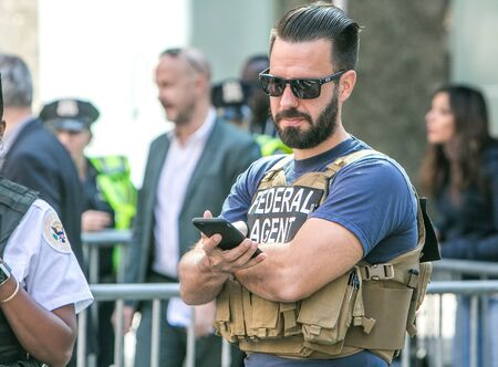 New York City, 9/27/2019: US federal agent is checking his phone while at a police checkpoint in Manhattan during UN General Assembly.