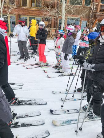 Park City, UT, 12/22/2019: Skiers stand in line to get on a chair lift at Deer Valley resort. 新闻类图片