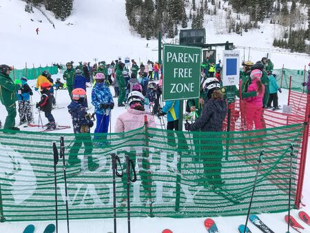 Park City, UT, 12/21/2019: Children and their ski instructors are assembling into groups at the drop off area before starting their day at Deer Valley resort.
