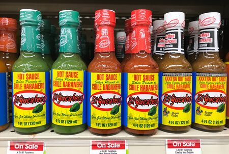 Park City, UT, 1/1/2020: Bottles of hot spicy sauces stand on a shelf of a supermarket. 免版税图像 - 138056007