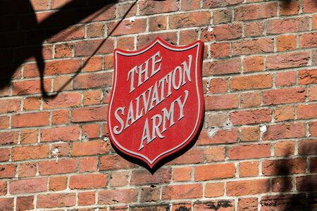New York City, 9/27/2019: The Salvation Army shield is mounted to an exterior brick wall above the entrance to its branch.