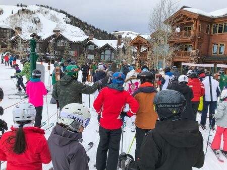 Park City, UT, 12/22/2019: Skiers have formed a line to get on a chair lift at Deer Valley resort. Editorial