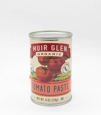 New York, 12/8/2019: Can of Muir Glen tomato paste stands against white background. 免版税图像 - 138056016