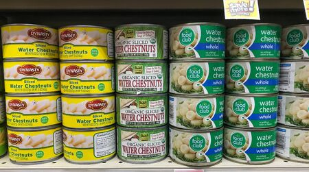 Park City, UT, 1/1/2020: Cans of water chestnuts stand on a shelf of a supermarket. Editorial
