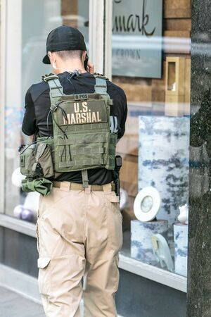 New York City, 9/27/2019: US marshal is talking on the phone while deployed to a police checkpoint near the UN headquarters Manhattan during General Assembly. 免版税图像 - 138056022