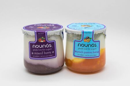 New York, 12/8/2019: Glass containers of Nounos yogurt stand against white background. Editorial